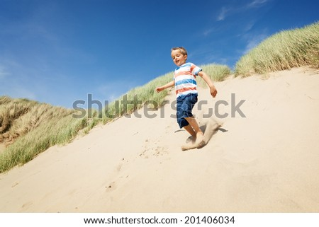 Boy running and jumping down sand dunes on a beach smiling and having fun - stock photo