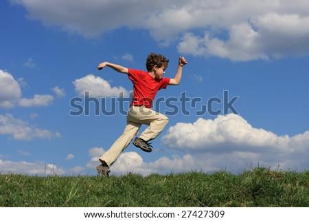 Boy running on green meadow - stock photo
