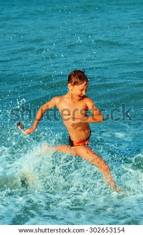 Boy running through the water at the beach