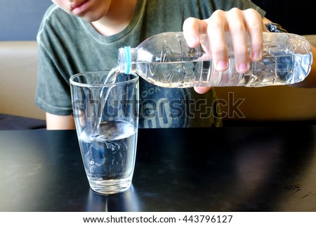 Boy's hand holding a bottle of water Pouring water into a glass