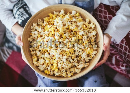 boy's hand holding a large bowl of popcorn - stock photo