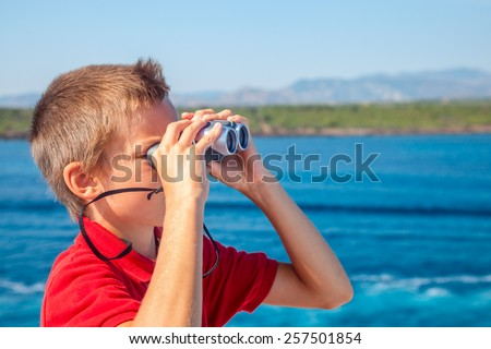 Boy sailing on cruise ship looking through binoculars - stock photo