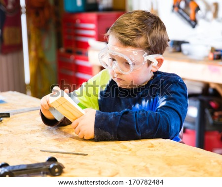 Boy sanding wooden block in workshop as he builds car for Pinewood Derby - stock photo