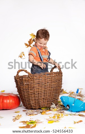 boy scatters autumn leaves