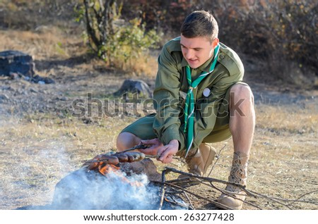Boy Scout in Uniform Crouching and Cooking Sausages on Sticks over Campfire - stock photo