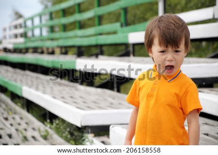 boy screaming in discontent, outdoor, summer time