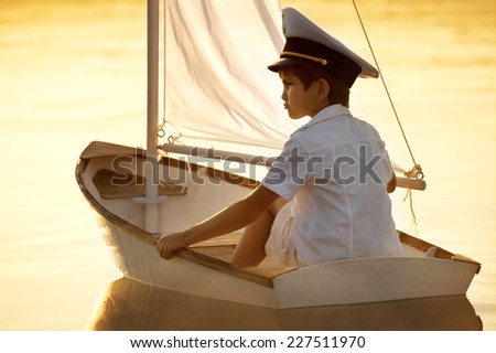 Boy seaman floats on a sailing boat at sunset on a warm evening summer - stock photo