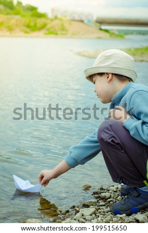 boy sends a paper boat - stock photo