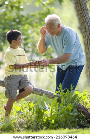 Boy sharing MP3 player with grandfather outdoors