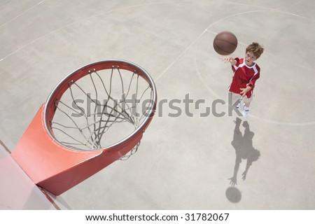 Boy shooting basketball while jumping - stock photo