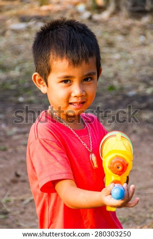 Boy shooting water gun in the summer time. - stock photo