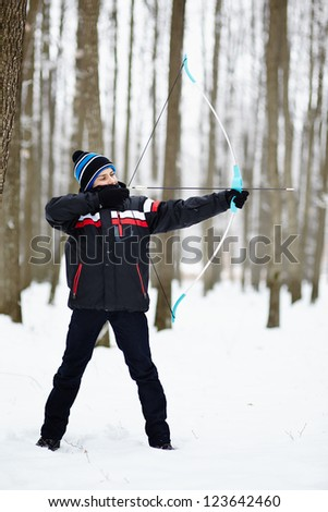 Boy shooting with his bow outdoor in the forest, in a winter day - stock photo
