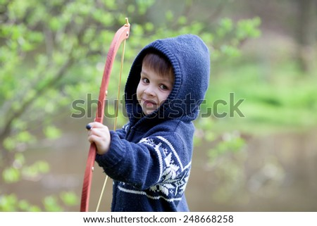 Boy shoots with bow at a target, in the open air  - stock photo