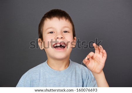 boy show lost tooth on a thread