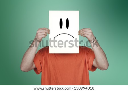 boy showing a blank paper with a sad emoticon in front of his face