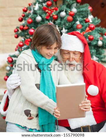 Boy showing digital tablet to Santa Claus in front of Christmas tree outdoors - stock photo