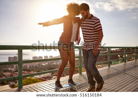 Boy showing girl how to skateboard while holding her up and her other arm straight out to balance herself