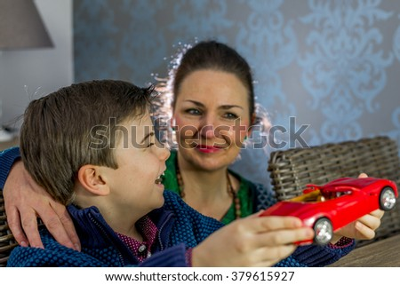 boy showing his model car to his mother, shallow depth of field