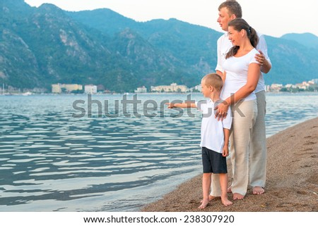 boy showing his parents at sea - stock photo