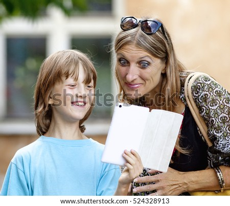 Boy Showing Something to Mother on Tablet
