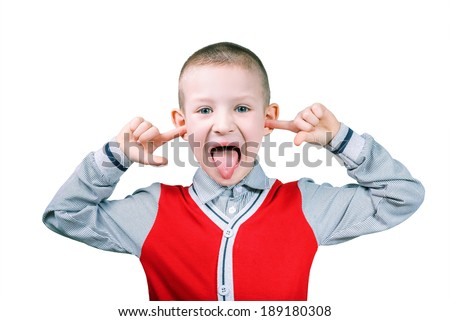 boy showing tongue with fingers in ears - stock photo