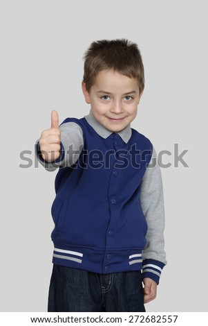 Boy shows thumb up on gray background - Endorsement, all is good