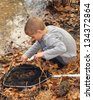 Boy sifiting through finds in his net at the edge of a pond - stock photo