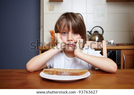 Boy sits at kitchen table and refuse to eat his meal - stock photo