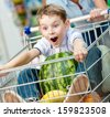 Boy sits in the shopping trolley with watermelon and other products bought by parents - stock photo