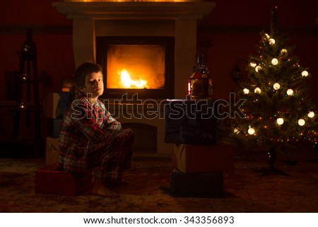 Boy sits near fireplace