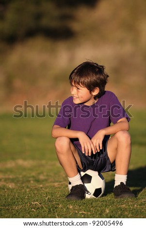 Boy sits on soccer ball looking to side in late afternoon sun - with copy space above and to left - stock photo