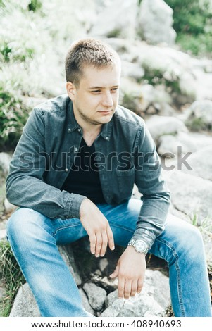 boy sits on the stone away in the mountains