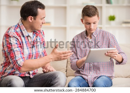 Boy sitting at sofa and using digital tablet while his father talking to him. - stock photo