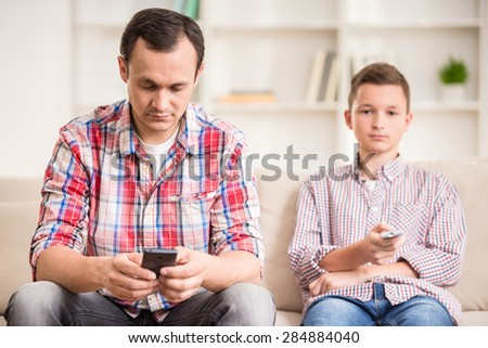 Boy sitting at sofa and watching television while his father using his phone. - stock photo