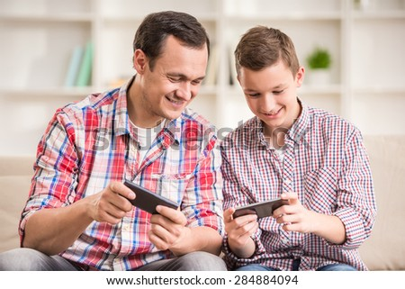 Boy sitting at sofa with his father and using phone. - stock photo