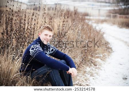 boy sitting at winter road - stock photo