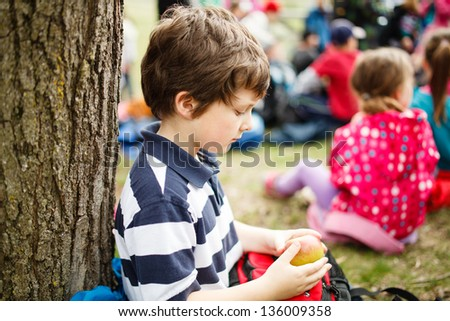 Boy sitting by a tree eating an apple on a school trip - stock photo