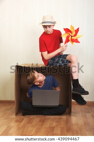 Boy sitting in a cardboard box with a laptop, boy sitting on the cardboard with a colorful windmill paper
