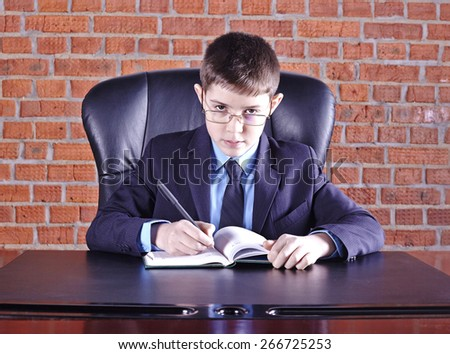 Boy sitting in a chair at the boss's table