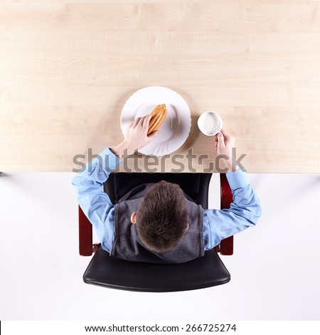 Boy sitting in a chair at the office table with tableware. Top view. - stock photo