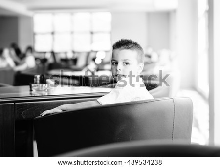 boy sitting in a chair in a restaurant shopping center and looking sideways
