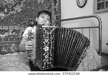 boy sitting in a cottage on the bed with an accordion - stock photo