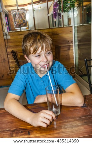 boy sitting in a restaurant and using a straw for drinking