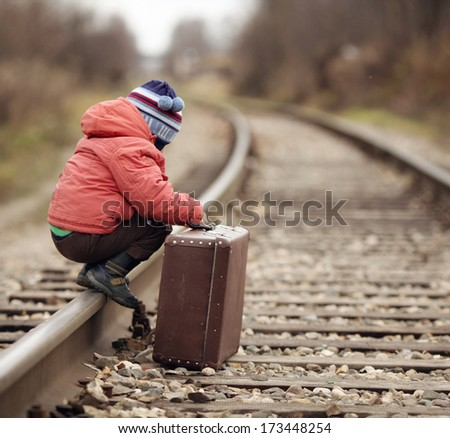 boy sitting in a suitcase near the railway journey - stock photo