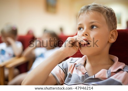 boy sitting in cinema armchair, holding fingers near mouth - stock photo