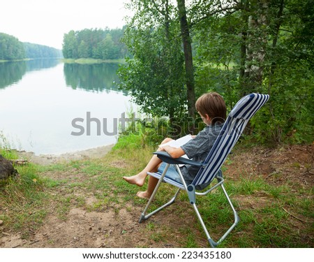 Boy sitting in deckchair reading a book on a lake shore - stock photo