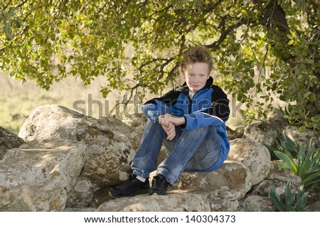 Boy sitting in nature on a rock under a tree