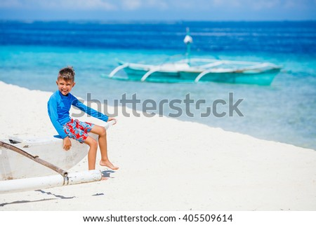 Boy sitting in old boat on the beach - stock photo