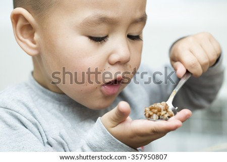 boy sitting in the kitchen and appetite eats
