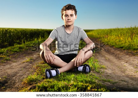Boy sitting in the middle of a countryside road